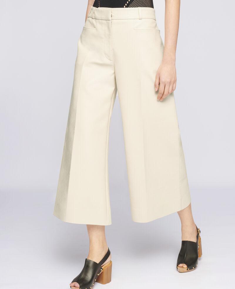 Pantaloni a gamba larga di colore beige, chiusura nascosta con zip e gancetto.